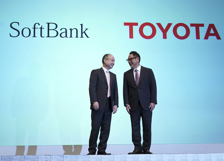 SoftBank Group Corp. Chairman Masayoshi Son (left) and Akio Toyoda, president of Toyota Motor Corp., chat during a photo session at a news conference in Tokyo on Oct. 4.