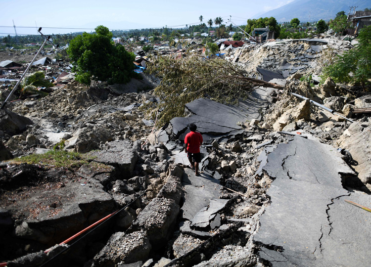 A man walks along a destroyed road in Palu, the capital of Indonesia's Central Sulawesi province, on Oct. 2 after an earthquake and tsunami hit the area on Sept. 28.