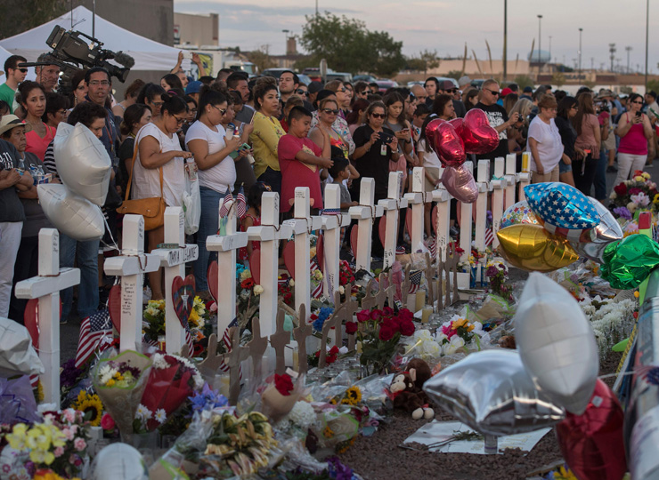 People pay their respects Aug. 5 at a makeshift memorial for victims of the Aug. 3 shooting that left 22 people dead at the Cielo Vista Mall Walmart in El Paso, Texas.