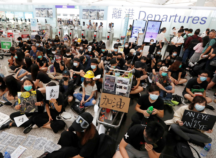 Anti-government protesters sit on the floor in front of security gates during a demonstration at Hong Kong Airport on Aug. 13.