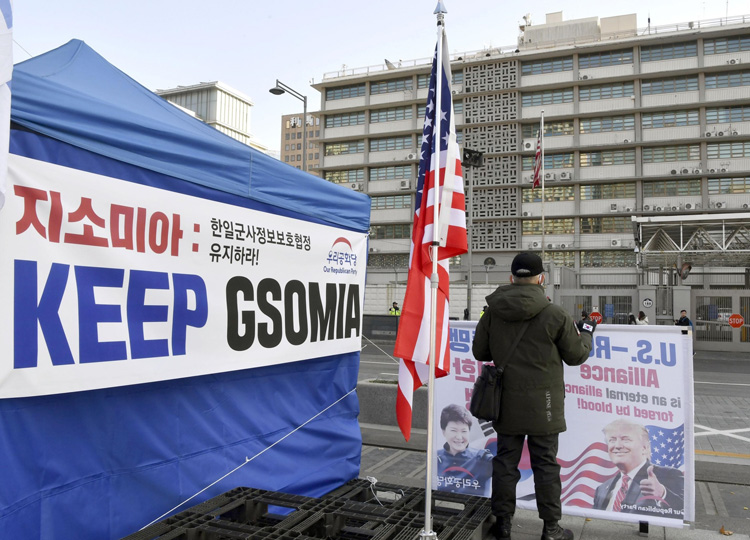 A man in Seoul stands in front of a sign demanding that the General Security of Military Information Agreement be kept, as the deadline for renewing the pact approaches on Nov. 22.