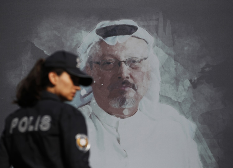 A Turkish police officer walks past a picture of slain Saudi journalist Jamal Khashoggi prior to a ceremony, near the Saudi Arabia consulate in Istanbul on Oct. 2.