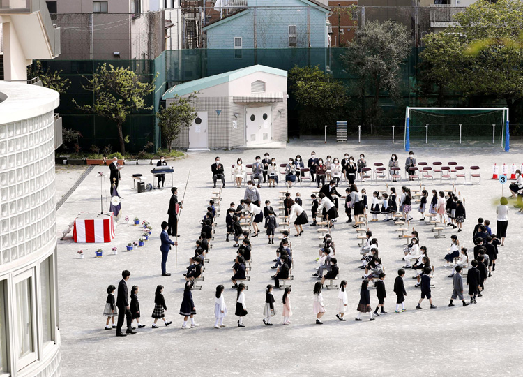 An enrollment ceremony for new students is held at the playground of Senju Sakura Elementary School in Tokyo on April 6 amid concerns over the new coronavirus.
