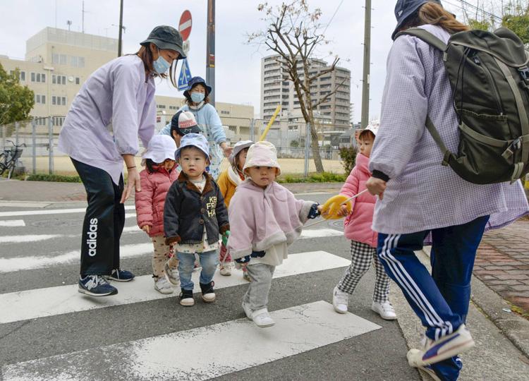 Preschool teachers guide preschoolers across a crosswalk in Osaka in February.