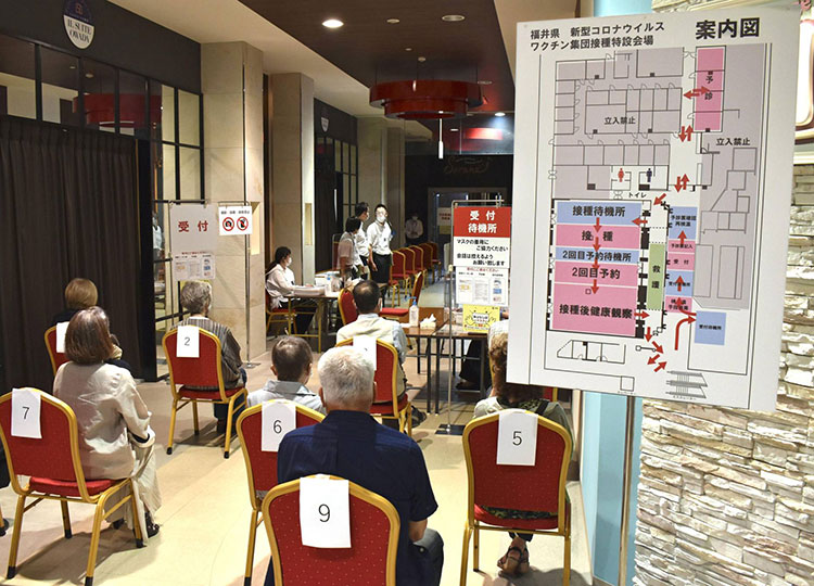 People wait to get vaccinated against COVID-19 at a mass inoculation site at a shopping mall in the city of Fukui in June.