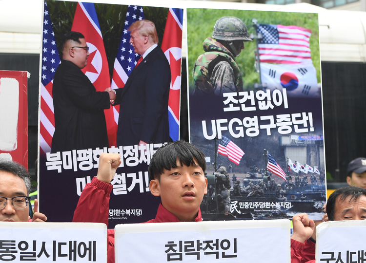 Activists hold placards showing images of the Trump-Kim summit (left) and a South Korea-U.S. joint military drill during a rally near the U.S. embassy in Seoul on June 15.