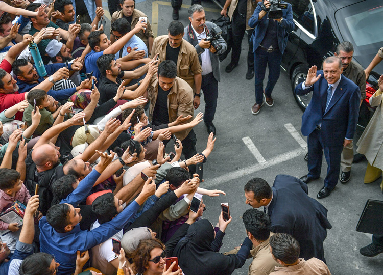 Turkish President Recep Tayyip Erdogan, leader of the Justice and Development Party (AKP) is greeted by supporters after casting his vote in Istanbul on June 24.
