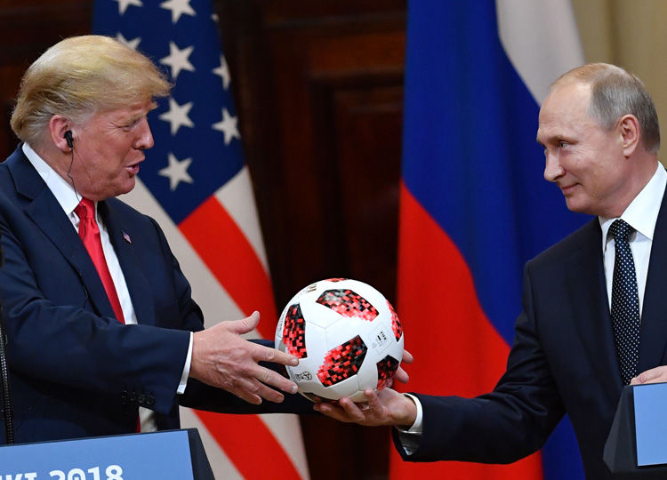 Russia's President Vladimir Putin (right) offers a ball from the 2018 World Cup to U.S. President Donald Trump during a joint press conference after a meeting at the Presidential Palace in Helsinki on July 16.