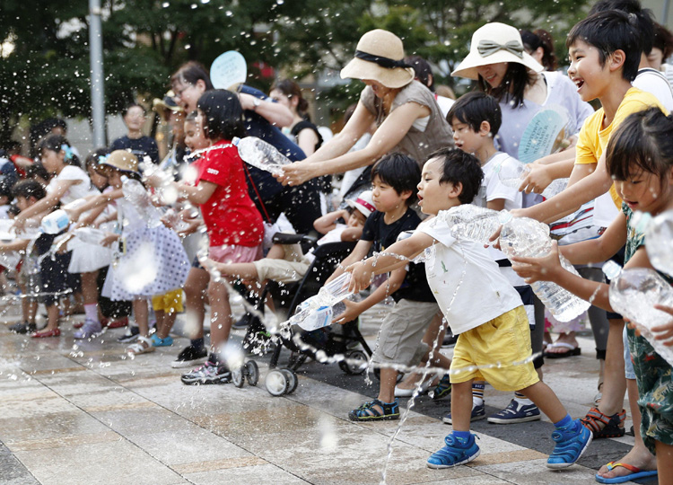 Children participate in an uchimizu (water-sprinkling) event held in Tokyo's Roppongi district on July 23 as Japan recorded its highest temperature.
