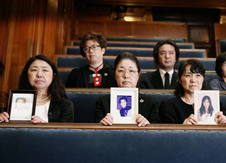 Relatives of karoshi (death from overwork) victims watch as the Diet enacts a labor reform bill on June 29.