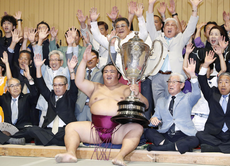 Sekiwake Mitakeumi celebrates with his supporters as he holds the Emperor's Cup after winning the Nagoya Grand Sumo Tournament.