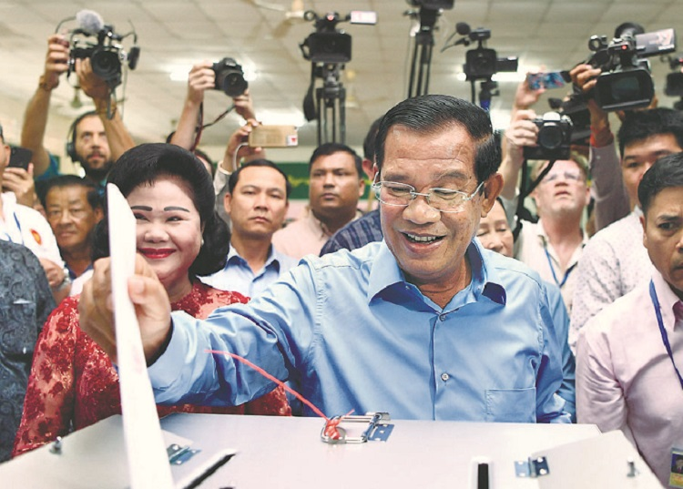 Cambodia's Prime Minister Hun Sen casts his vote at a polling station in Phnom Penh on July 29 as his wife Bun Rany watches.