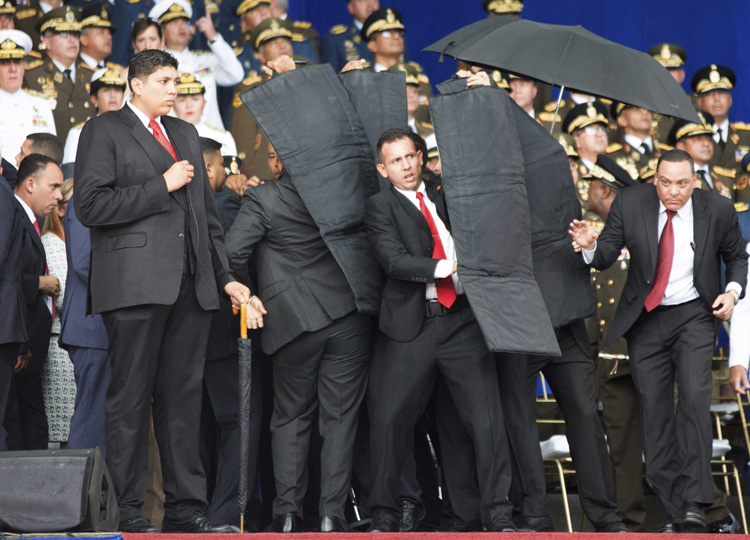 Security personnel surround Venezuela's President Nicolas Maduro during an incident as he was giving a speech in Caracas on Aug. 4.