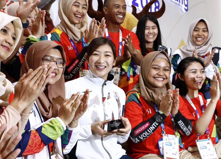 Rikako Ikee (center) poses for a photograph with volunteers after being chosen as Most Valuable Player at the Asian Games in Jakarta on Sept. 2.