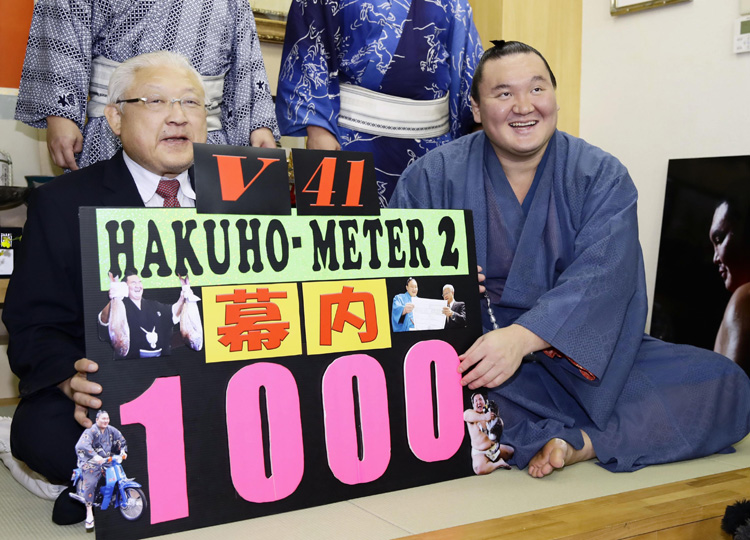 Hakuho celebrates winning an unprecedented 1,000 bouts in Sumo's top division with stablemaster Miyagino in Tokyo's Sumida Ward on Sept. 22, the day he won his 41st championship.