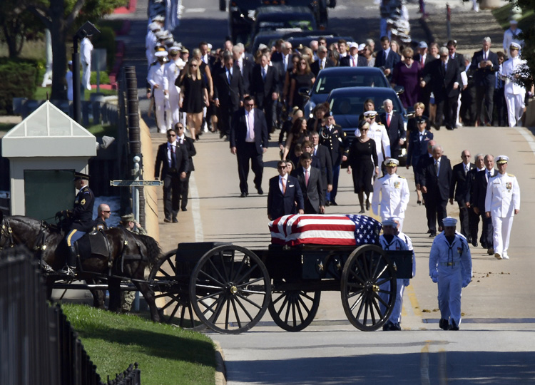 Family members follow a horse-drawn wagon that carries the casket of Sen. John McCain as it proceeds to the United States Naval Academy cemetery in Annapolis, Maryland.