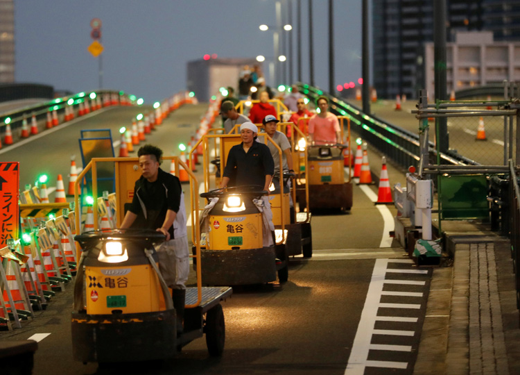 "Fishmongers drive ""turret truck"" flatbeds to Toyosu market during the relocation from Tsukiji in Tokyo on Oct. 7."