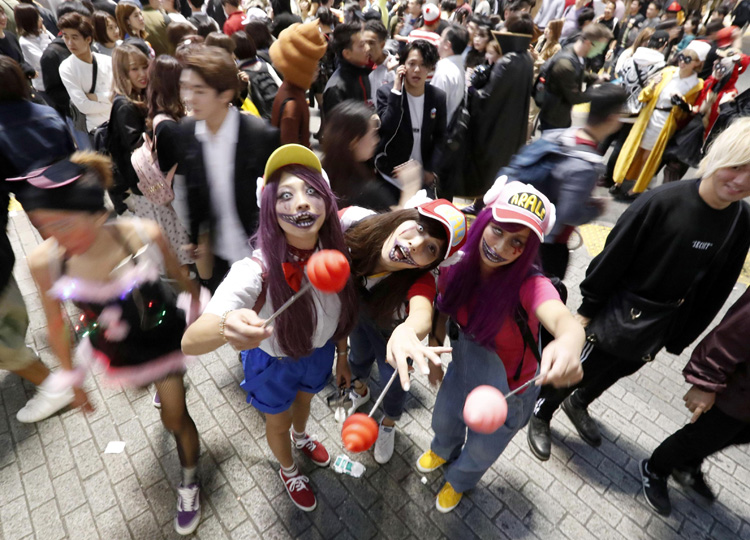 People dressed up in costumes pose for a photo in Tokyo's Shibuya Ward on Oct. 28 during a Halloween celebration.