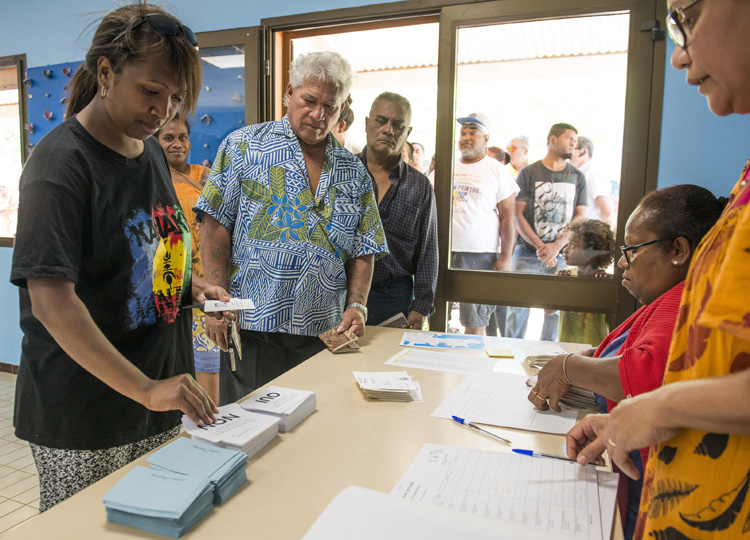 People line up at a polling station in Noumea to cast their votes in a referendum on Nov. 4 over whether New Caledonia should become independent from France.