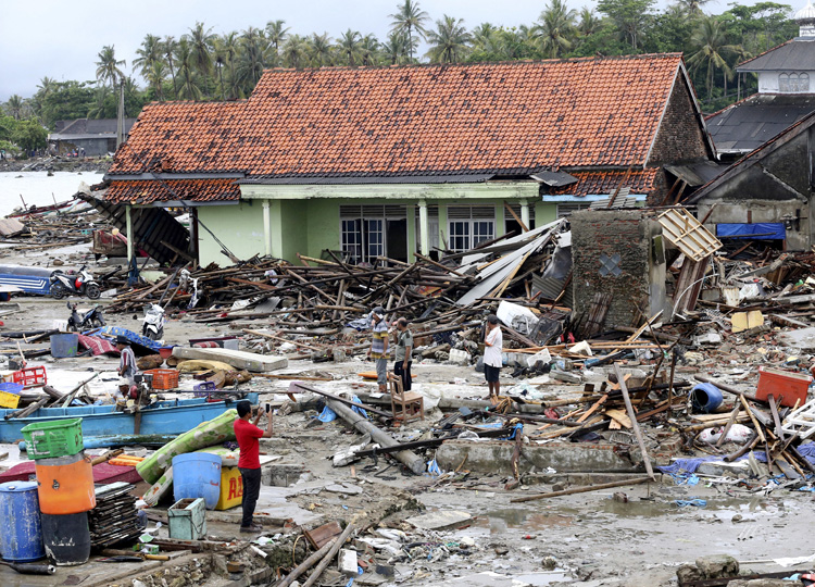 People inspect the damage at a tsunami-ravaged village in Sumur, Indonesia, on Dec. 25.