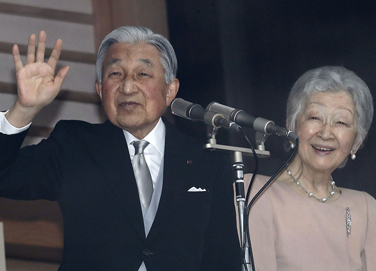 Emperor Akihito (left), accompanied by Empress Michiko, waves to well-wishers as they appear on the balcony of the Imperial Palace to mark the Emperor's 85th birthday in Tokyo on Dec. 23. AP