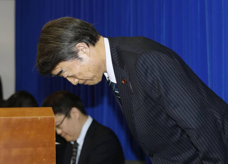 Labor minister Takumi Nemoto apologizes during a news conference at the ministry in Tokyo on Jan. 11.