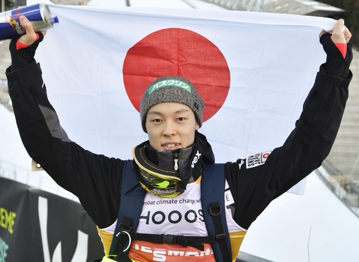 Ryoyu Kobayashi holds up the national flag of Japan after clinching the men's ski jumping World Cup title on March 10 in Oslo.