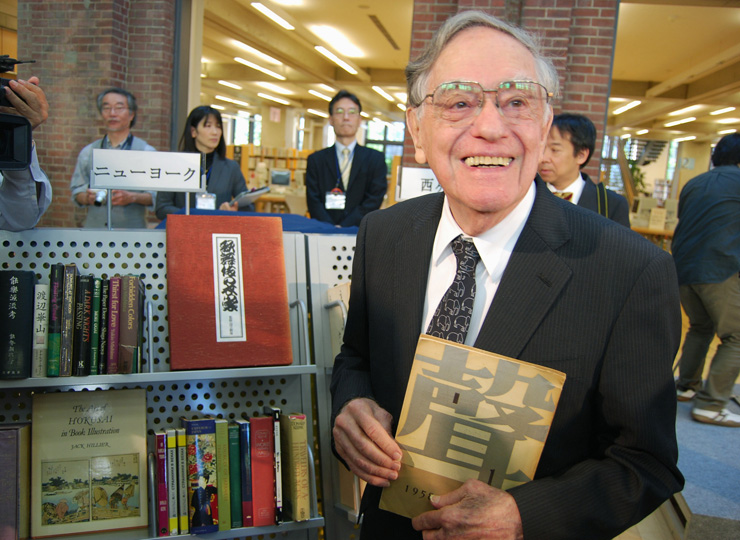 Donald Keene smiles in front of a bookcase displaying some of the 600 works he donated to Kita City Library in Kita Ward, Tokyo, in October 2011.
