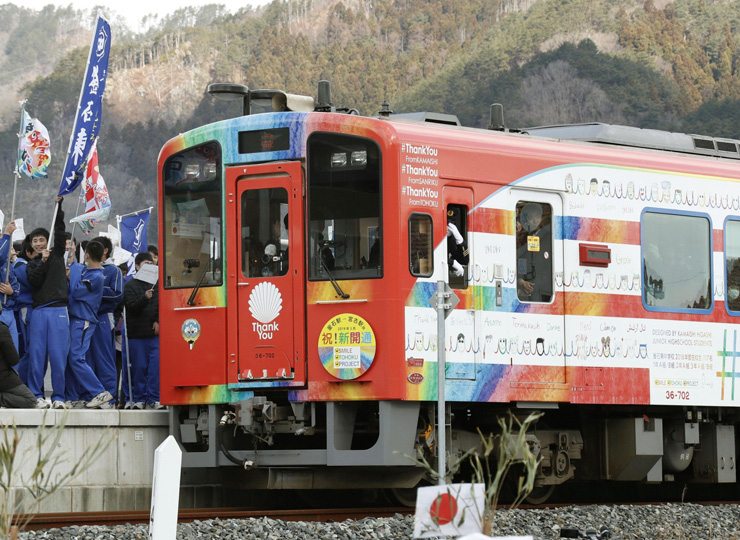 Local students welcome a Sanriku Railway Co. train decorated with a design they helped make at Unosumai Station in Kamaishi, Iwate Prefecture, after regular train services resumed on the Rias Line.
