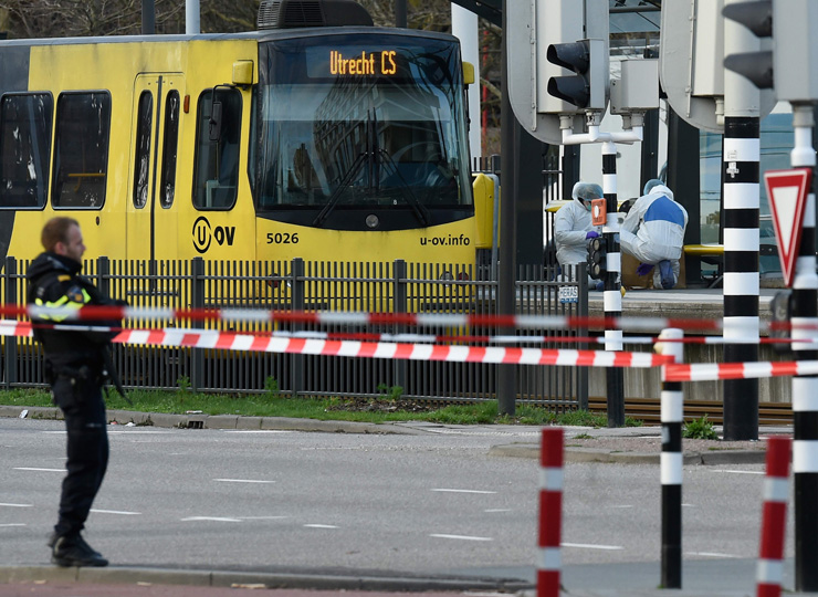Policemen and rescuers are at work on March 18 in Utrecht, near a tram where a gunman opened fire, killing three people.