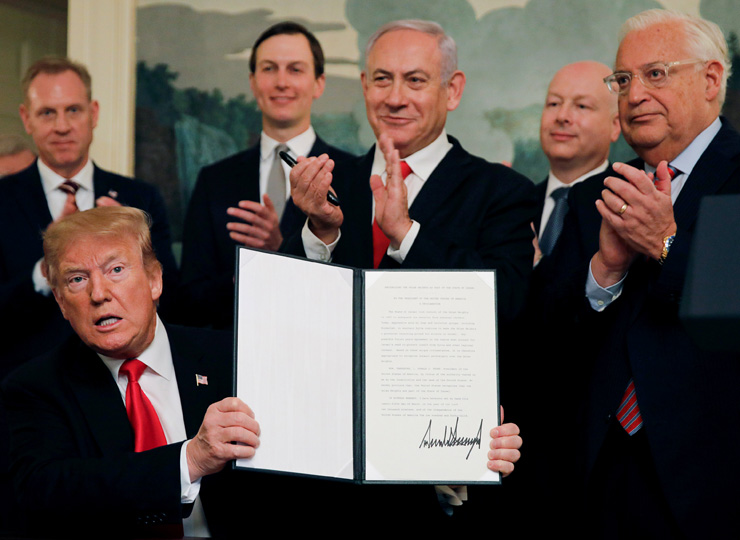 U.S. President Donald Trump (left) holds a proclamation as Israeli Prime Minister Benjamin Netanyahu (center) and others applaud during a ceremony at the White House on March 25.