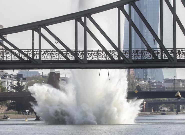 住民たちが安全な距離から見守る中、爆発により水柱が上がった。