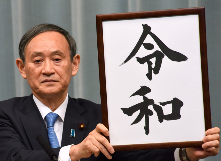 Chief Cabinet Secretary Yoshihide Suga holds up a placard showing the kanji for Reiwa at a news conference April 1 at the Prime Minister's Office.