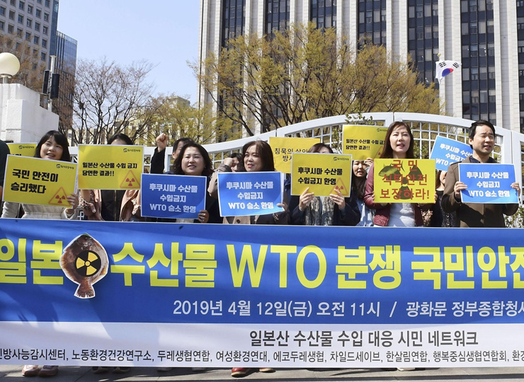 Members of a South Korean citizens' group in Seoul celebrate the World Trade Organization's decision in favor of continuing an import ban on Japanese seafood on April 12.