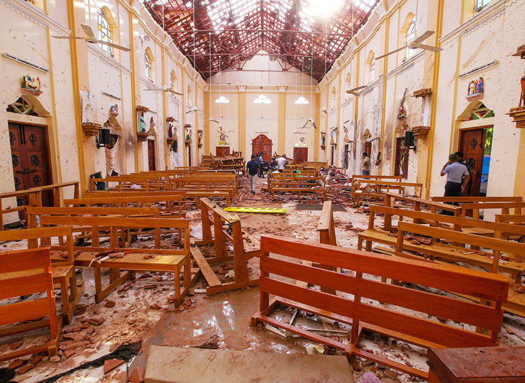 Crime scene officials inspect the site of a bomb blast inside St. Sebastian's Church in Negombo, Sri Lanka, on April 21.