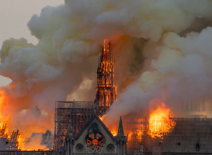 Smoke billows as flames burn through the roof of the Notre Dame Cathedral in Paris on April 15 in Paris.