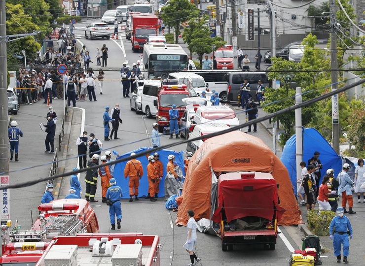 Public officers and firefighters attend the scene of a mass stabbing in Kawasaki near a school bus stop on May 28.