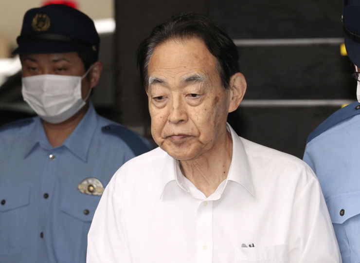 Hideaki Kumazawa, 76, is escorted out of Nerima Police Station in Tokyo on June 3, to be sent to prosecutors.