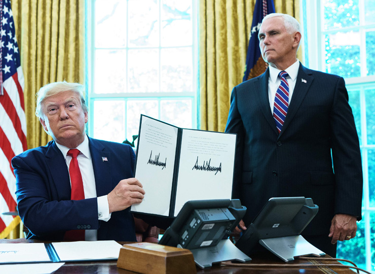 U.S. President Donald Trump holds up an executive order for sanctions on Iran's supreme leader in the Oval Office of the White House on June 24.