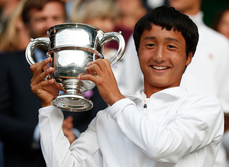 Shintaro Mochizuki raises the winner's trophy after beating Spain's Carlos Gimeno Valero in their boys' singles final match of the 2019 Wimbledon Championships in southwest London on July 14.