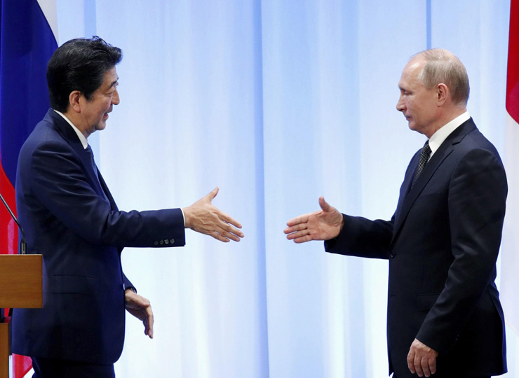 Prime Minister Shinzo Abe and Russian President Vladimir Putin shake hands in Osaka on June 29 after a bilateral meeting on the sidelines of the Group of 20 summit.
