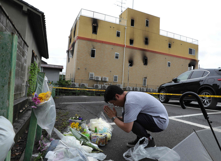 A man prays July 19 next to flowers and tributes laid near an animation company studio in the city of Kyoto where more than 30 people died in a July 18 fire.