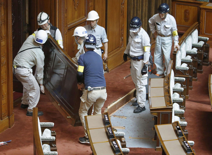 Workers remove seats from the Upper House chamber on July 28 as part of renovations for two newly elected lawmakers with severe physical disabilities.