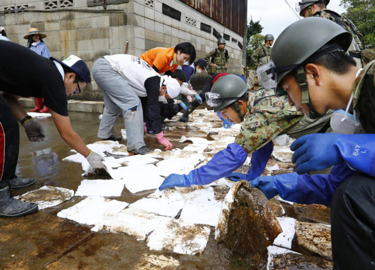 Local residents and Self-Defense Force members place absorption sheets on a street in Omachi, Saga Prefecture, to remove oil washed away from a flooded ironworks.