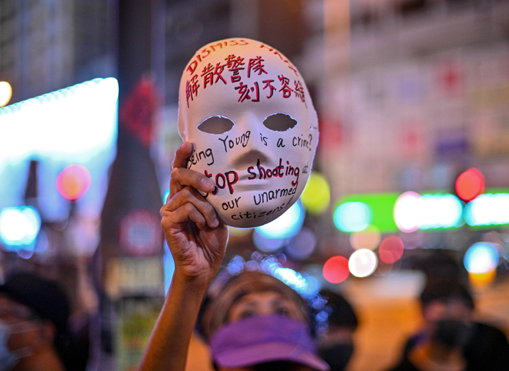 A woman holds a mask with slogans written on it as protesters gather outside Mong Kok Police Station in Hong Kong on Oct. 5, a day after the city's leader outlawed face coverings at protests.