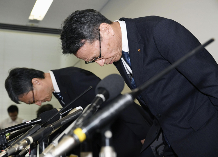 Kansai Electric Power Co. President Shigeki Iwane (right) bows at a news conference held in Osaka on Sept. 27.