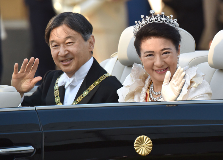 Emperor Naruhito (left) and Empress Masako wave during a royal parade in Tokyo on Nov. 10.