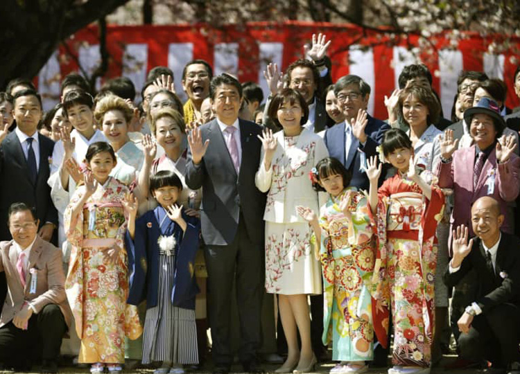Prime Minister Shinzo Abe (center) and his wife, Akie, pose for a photo with attendees at a cherry blossom-viewing event held April 13 at Shinjuku Gyoen National Garden in Tokyo.