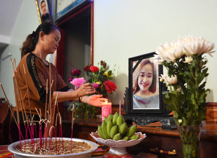 A relative lights an incense stick in front of a portrait of Bui Thi Nhung, who is feared to be among the 39 people found dead in Britain.