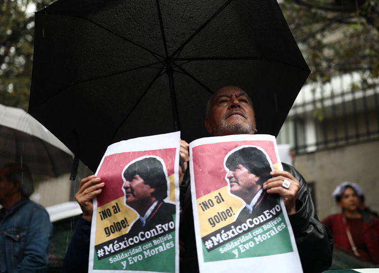 A man holds a sign in support of Bolivian President Evo Morales after he announced his resignation on Nov. 10, outside the Bolivian Embassy in Mexico City on Nov. 11.
